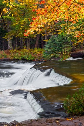 Colorful autumn foliage surrounds a cascade at Bond Falls, a very beautiful multistage waterfall in Michigan's western Upper Peninsula.
