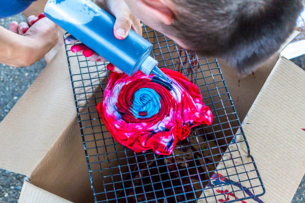 adding paint to tie-dye t-shirt